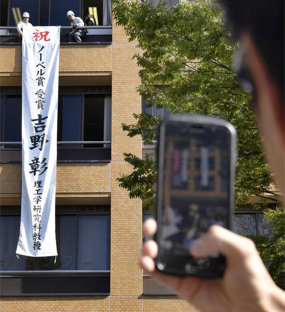 吉野彰さんが教授を務める名古屋市の名城大に掲げられた祝福の懸垂幕。スマートフォンで撮影する学生の姿も=10日午前