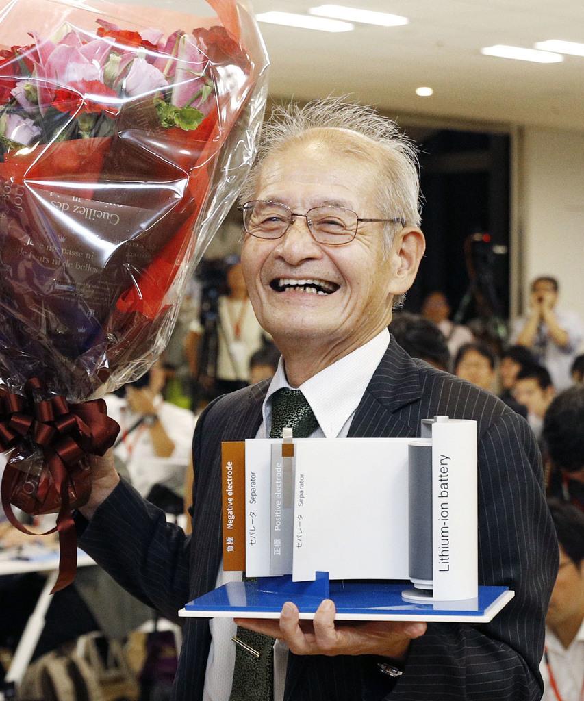 ノーベル化学賞の受賞が決まり、リチウムイオン電池の模型(もけい)を手に笑う吉野彰さん=9日、東京都千代田区