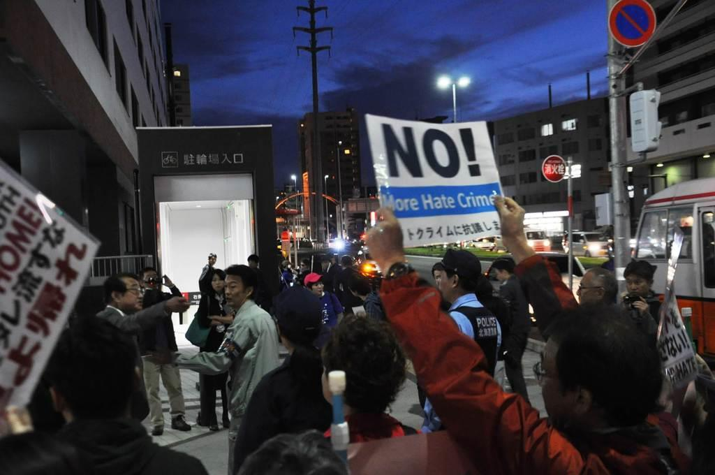 アイヌ新法に疑義を呈する講演会の会場前で、一部の参加者と「ヘイトスピーチだ」と主張する人々との間に割って入る北海道警=札幌市白石区(寺田理恵撮影)