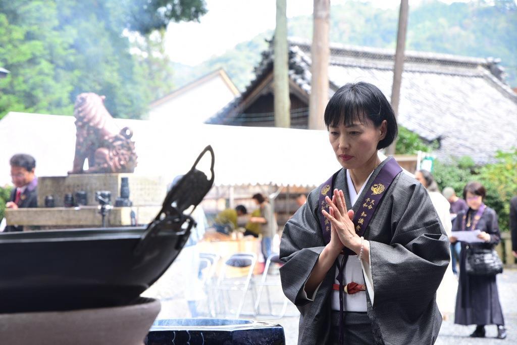 願いを書いた短冊を焚べ、手を合わせて発願する井戸理恵子さん