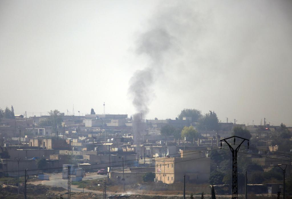 シリア北東部ラス・アルアインで、トルコ軍の砲撃の間に上がった煙=10日、トルコ側から撮影(AP)