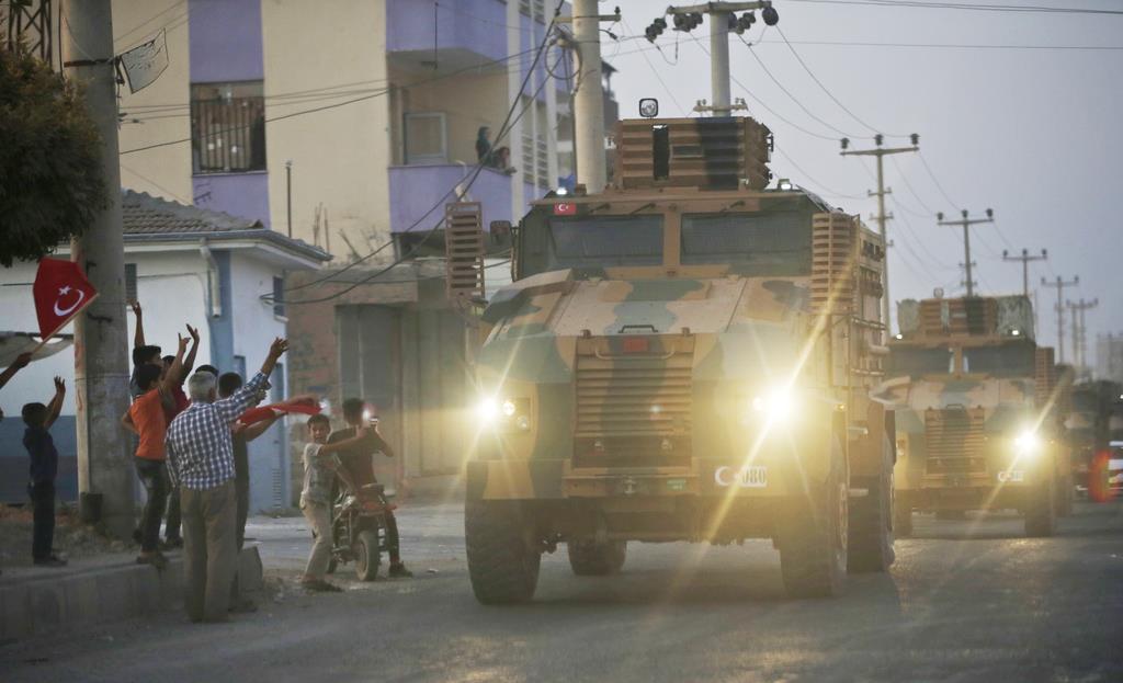 9日、トルコ軍の車列と、それに対して手を振るトルコ・シリア国境の町、アクチャカレの地元住民ら(AP)