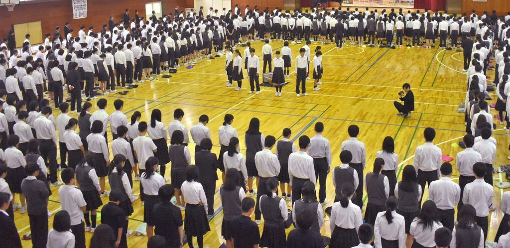 男子生徒が通っていた中学校で開かれた全校集会で黙祷をささげる生徒たち=11日午前、大津市