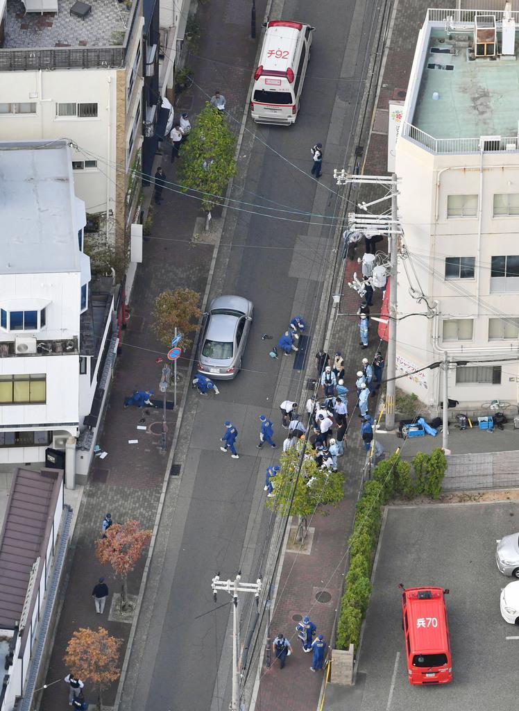 暴力団関係者の銃撃事件現場を調べる兵庫県警の捜査員ら=10日、神戸市