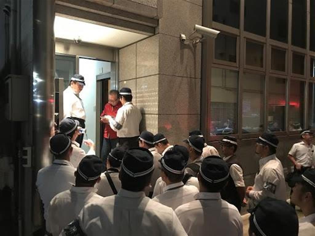 組事務所の使用制限について山健組関係者に伝える兵庫県警の捜査員=11日夜、神戸市中央区