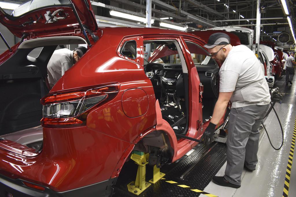 日産自動車の英サンダーランド工場の生産ラインで自動車の製造に取り組む従業員=10日(共同)