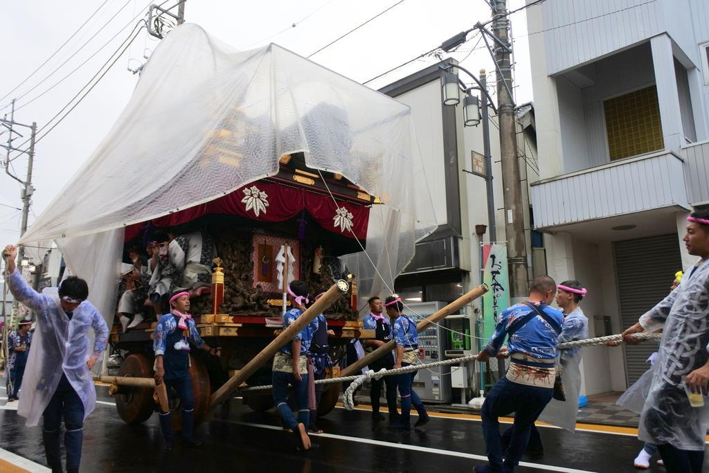 雨の中行われた「佐原の大祭」で、大人形にビニールシートをかけた状態で引き回される山車=11日、千葉県香取市(城之内和義撮影)
