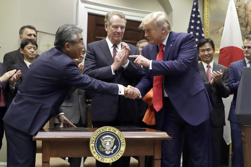 10月7日、米ホワイトハウスで行われた日米貿易協定の署名式に出席した(手前左から)杉山晋輔駐米大使、ライトハイザー通商代表、トランプ大統領(AP=共同)
