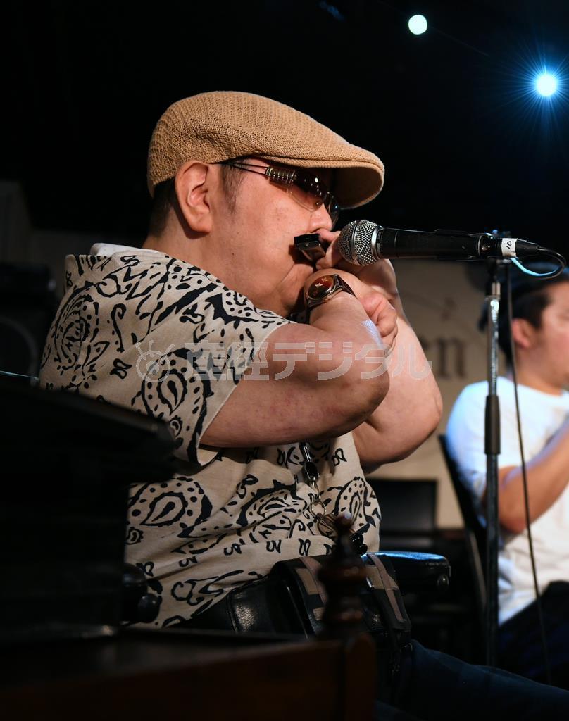 ワークショップで豪快な演奏を披露する山下純一さん。右手の甲にハーモニカを乗せ左手と口で音を包む独特の奏法だ =京都市中京区のライブハウス「モダンタイムス」(永田直也撮影)