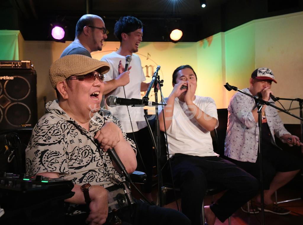 ハーモニカのワークショップで奏法をアドバイスしながら笑顔を見せる山下純一さん(左) =京都市中京区のライブハウス「モダンタイムス」(永田直也撮影)