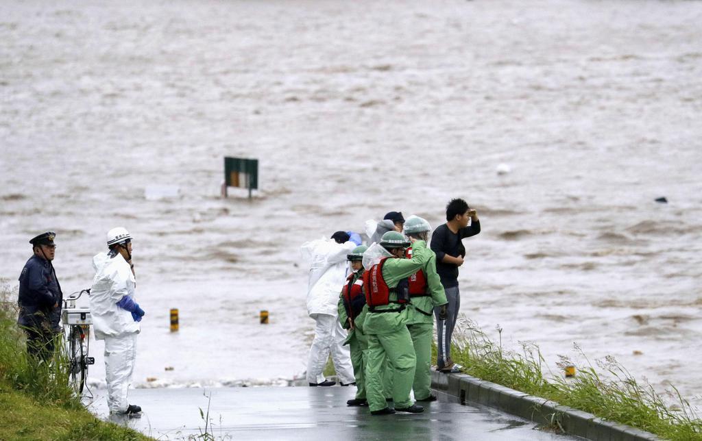 台風19号の影響で増水した多摩川で、流れを見つめる人たち=12日午後4時40分、東京都大田区