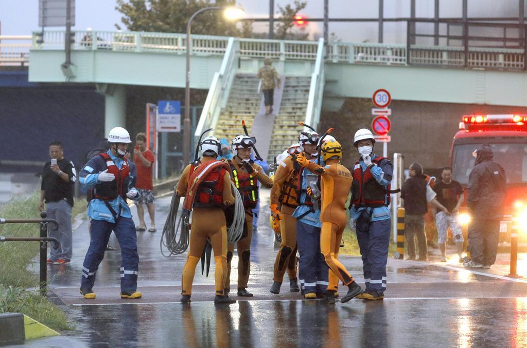 台風19号の影響で増水した多摩川の周辺に駆けつけた消防隊員ら=12日午後4時51分、東京都大田区