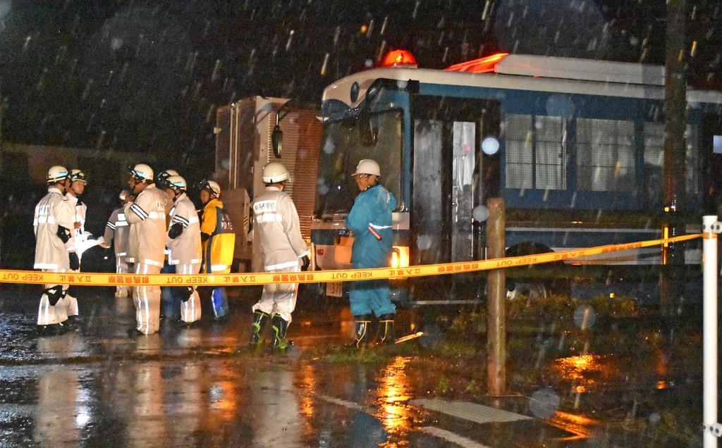 土砂崩れが発生した群馬県富岡市の現場付近に集まる警察官ら=12日午後8時19分