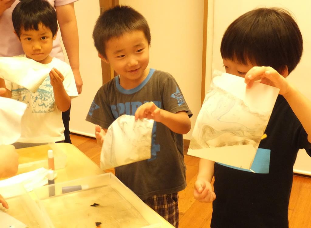 移し取ったマーブリング模様を見せ合う園児=東京都港区の「にじのいるか保育園 芝浦」