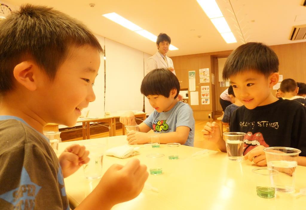 水の入ったコップに短い毛糸を入れて、水に浮く様子を観察=東京都港区の「にじのいるか保育園 芝浦」
