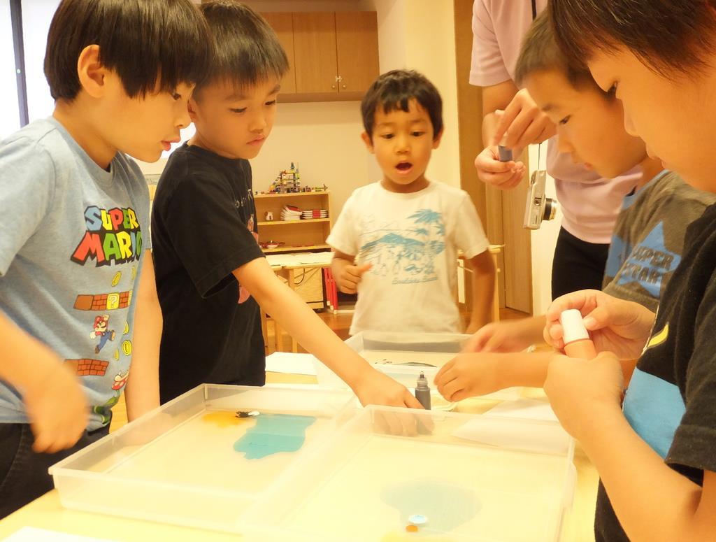 マーブリングの実験。表面張力と界面活性剤による模様の変化に興味津々=東京都港区の「にじのいるか保育園 芝浦」