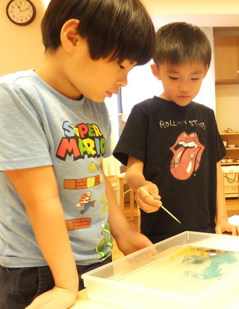水面に絵の具を浮かせ、洗剤を付けた竹串で表面をつついて模様の変化を観察する園児=東京都港区の「にじのいるか保育園 芝浦」