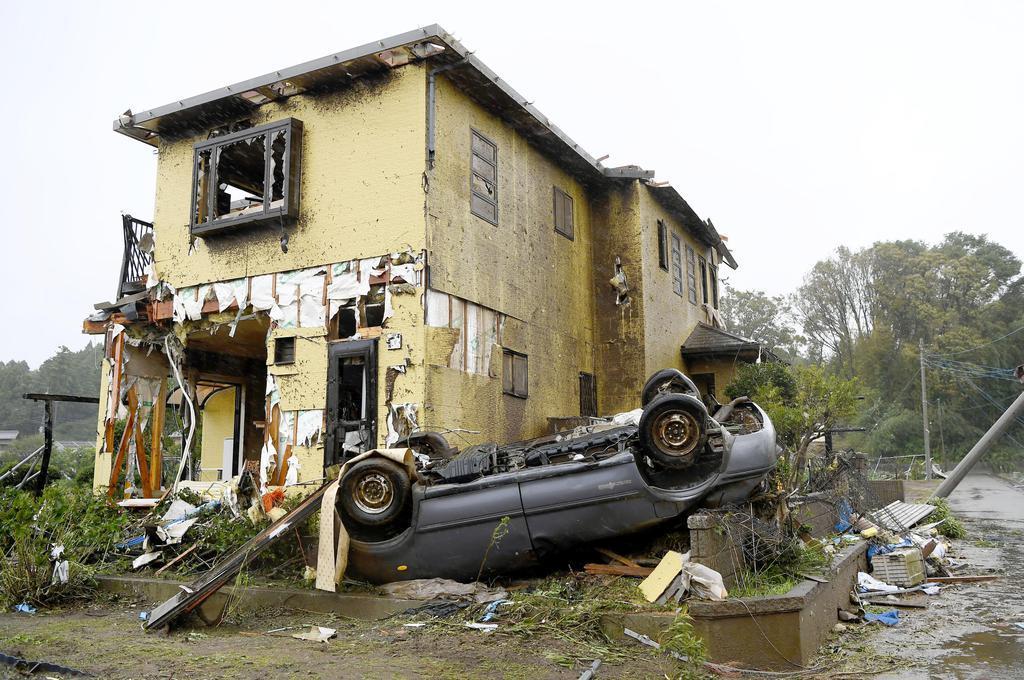 竜巻とみられる強風により被害を受けた住宅と横転した車=12日午前11時51分、千葉県市原市