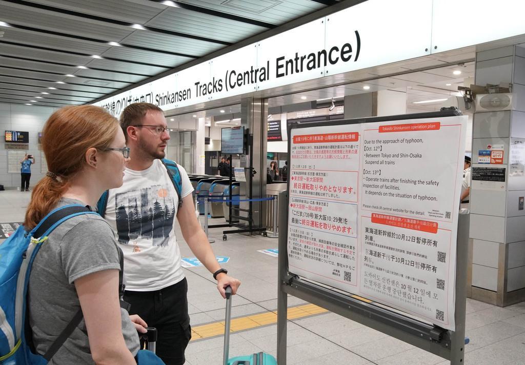 台風19号の上陸に伴い、新幹線運休のポスターを見る外国人の乗客=12日午前、大阪市淀川区のJR新大阪駅(恵守乾撮影)