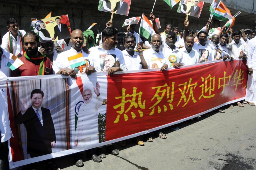 インド南部チェンナイの空港の外で、中国の習近平国家主席を歓迎する横断幕を掲げる人たち=11日(AP)
