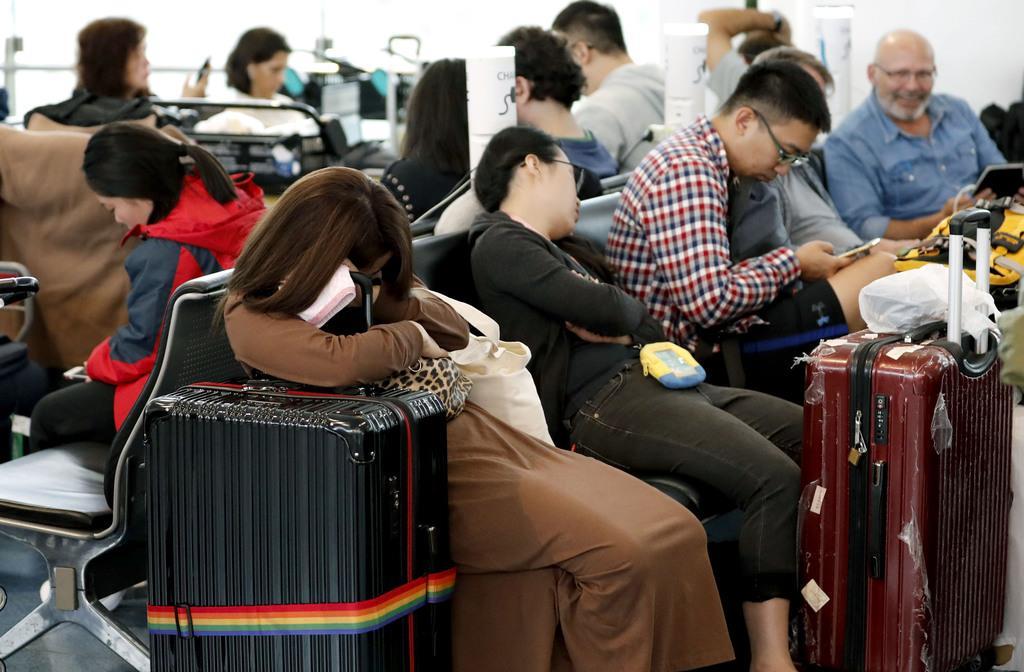 台風19号の接近でほとんどの便が欠航になった羽田空港国際線ターミナルで、仮眠をとる旅行客ら=12日午前10時41分