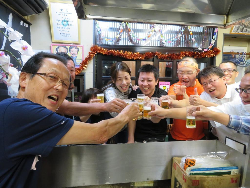 祝杯を挙げるファンら。巨人が勝てば、米澤さん(左)がビールを振る舞う=大阪府豊中市
