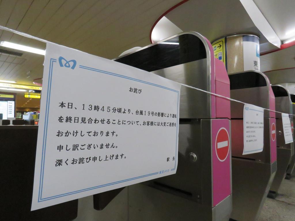 12日午後、閉鎖された東京メトロ丸ノ内線東京駅の改札口には運転見合わせを表示する紙が掲げられた