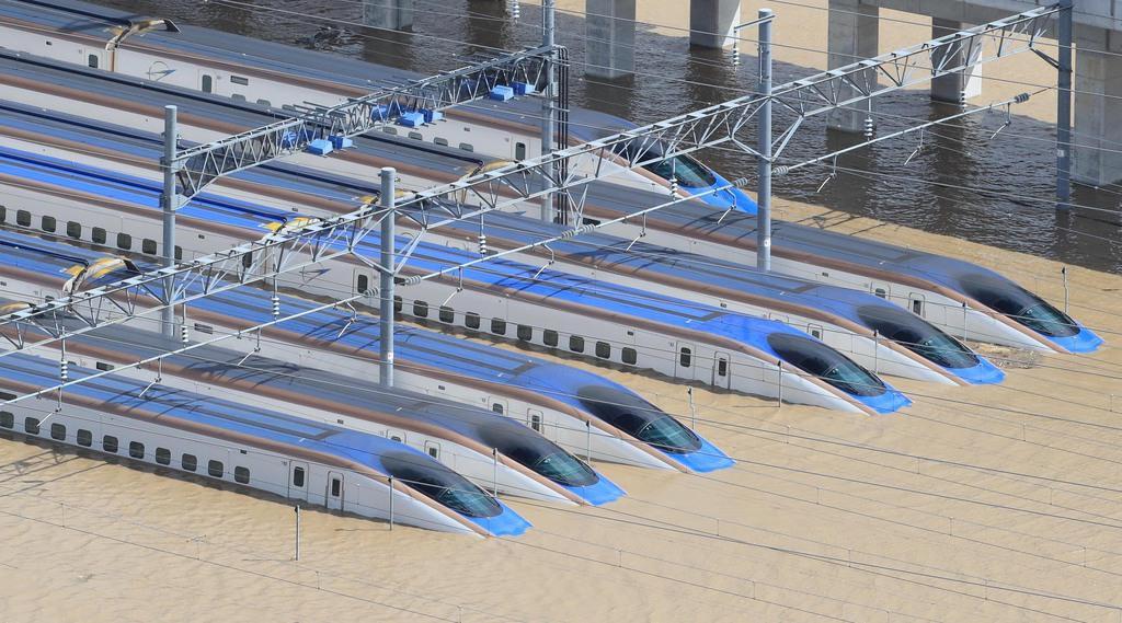 台風19号による大雨で水に漬かった車両基地に並ぶ新幹線=13日午前8時6分、長野市赤沼(共同通信社ヘリから)