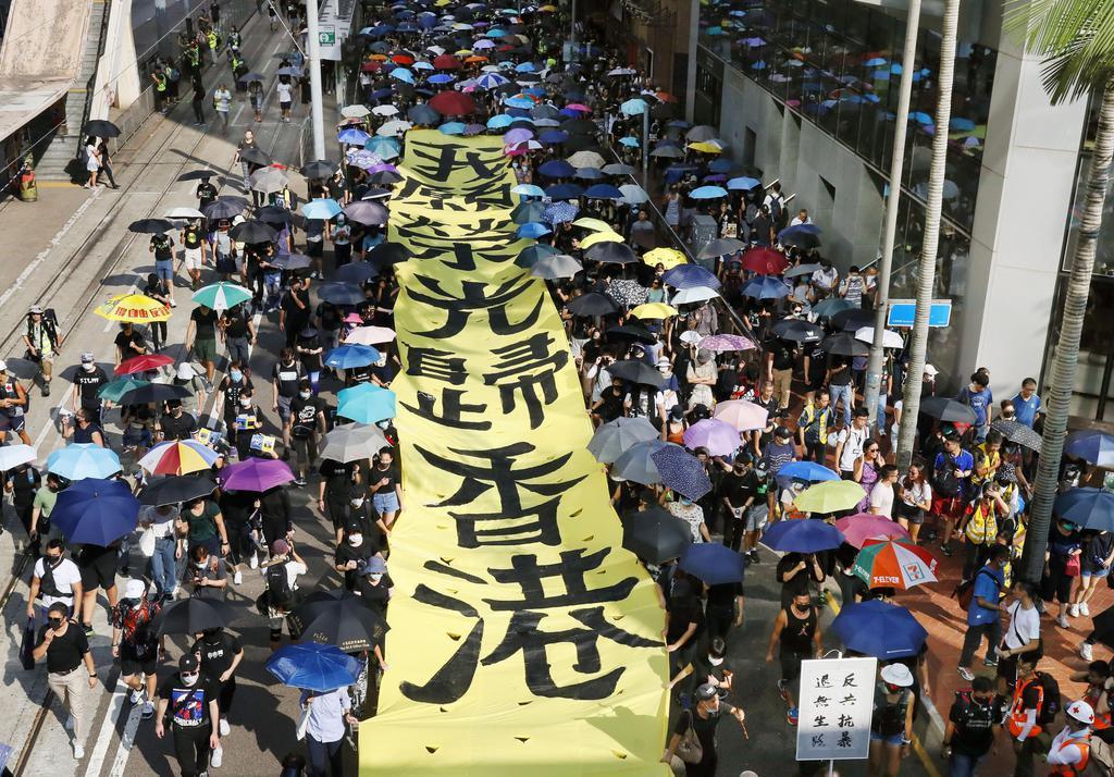 香港で「覆面禁止法」の施行などに抗議し、スローガンを掲げて通りを歩く人たち=5日(共同)