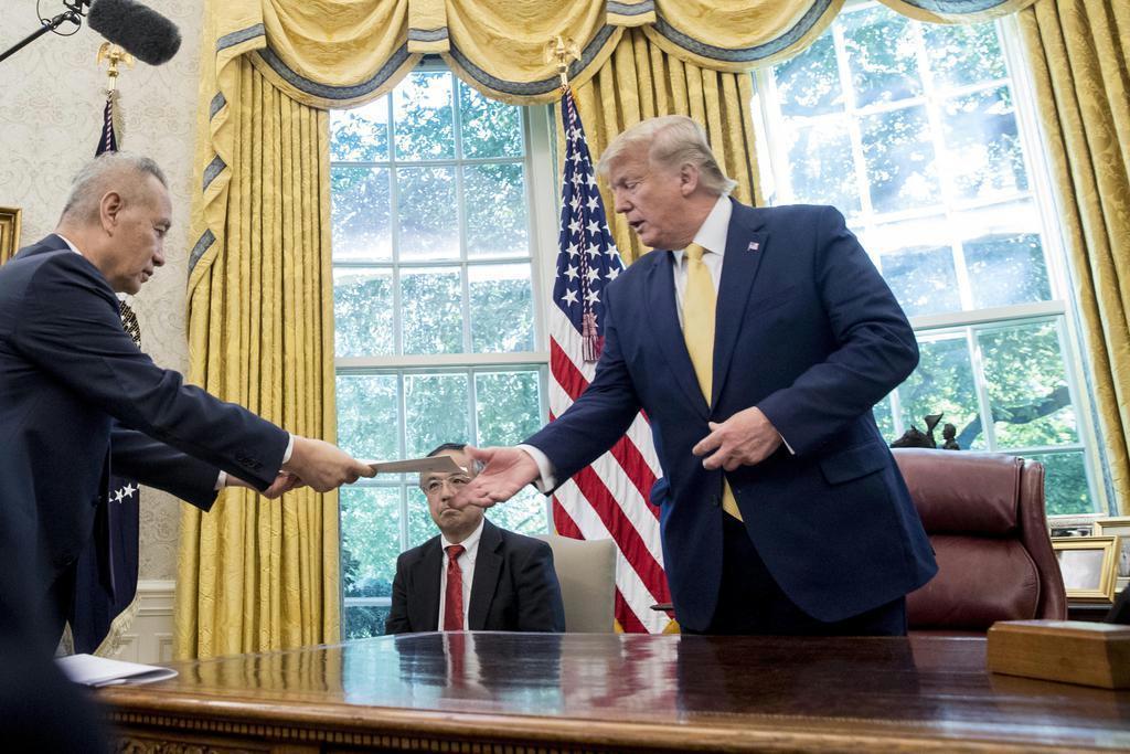 中国の劉鶴副首相(左)から書簡を受け取るトランプ米大統領=11日、米ホワイトハウス(AP)