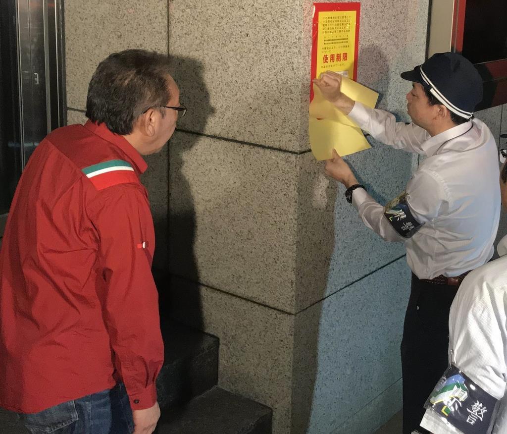 指定暴力団神戸山口組直系「山健組」事務所に使用制限を知らせる標章を貼る兵庫県警の捜査員=11日、神戸市中央区