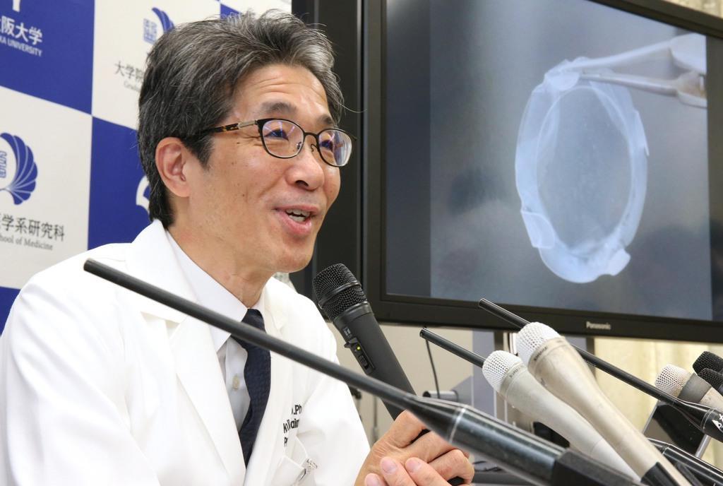 iPS細胞から作製した角膜上皮細胞シート(右画面)を用いた移植について説明する、大阪大学の西田幸二教授=8月29日、大阪府吹田市(前川純一郎撮影)