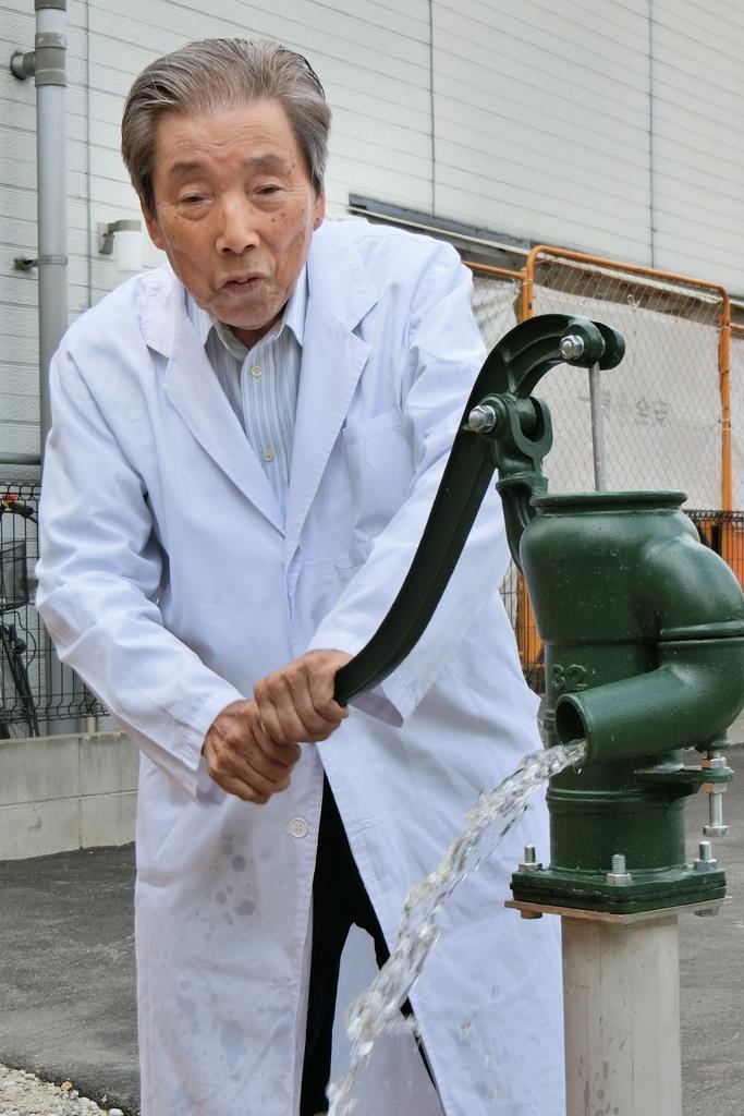 災害に活用するため整備した井戸から手押しポンプで水を出す院長の柴賢爾さん=大阪市旭区