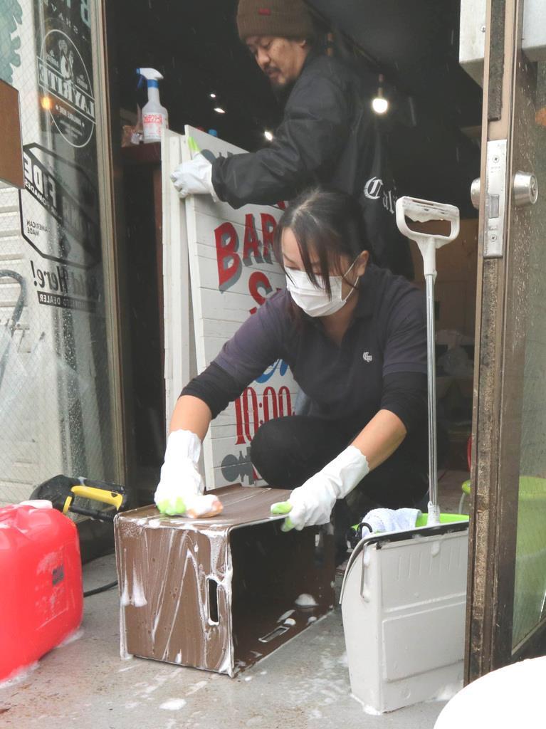 雨の中、浸水した理容店の片付けに追われる佐藤さん夫妻=19日、福島県郡山市(芹沢伸生撮影)