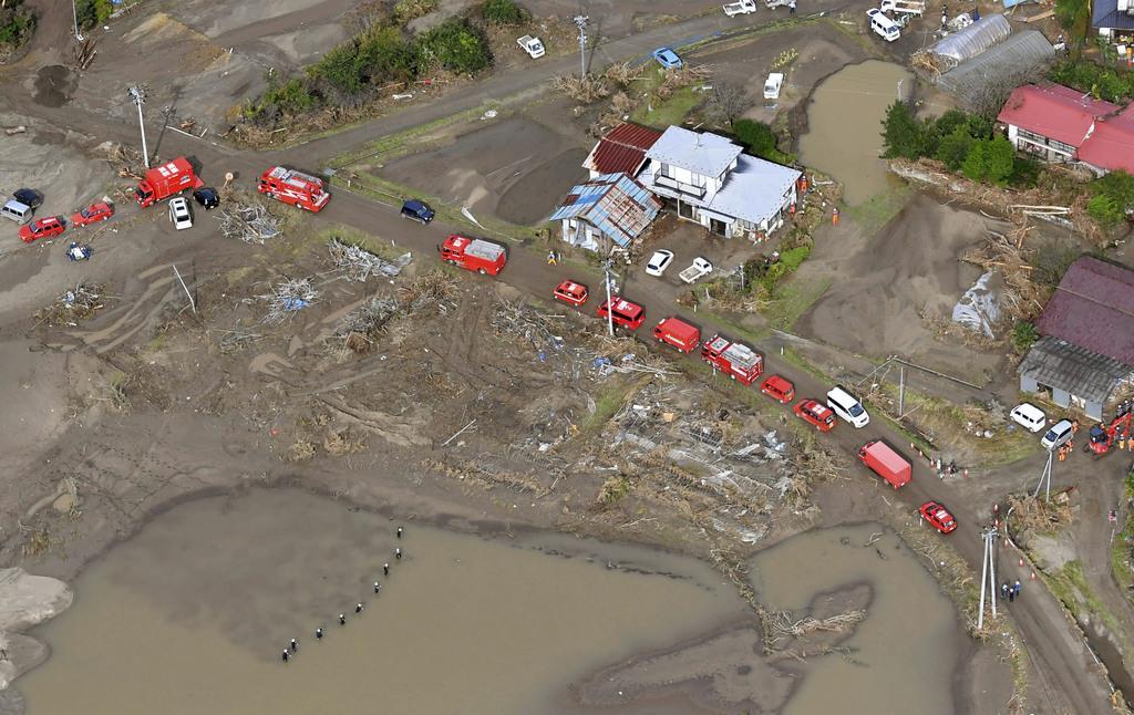 海上自衛隊員らが捜索する泥水がたまった田んぼ=20日午前、宮城県丸森町