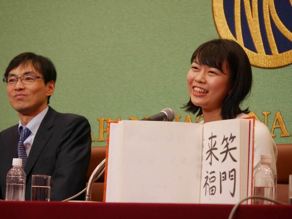 日本記者クラブで会見した上野愛咲美女流棋聖は「笑門来福」と揮ごうした。左は師匠の藤沢一就八段