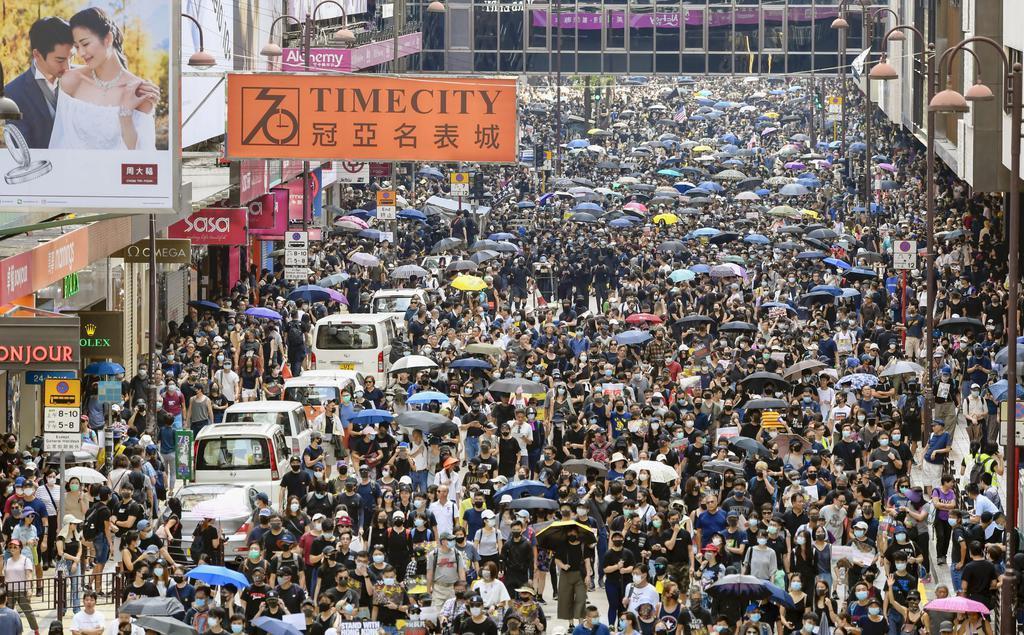 香港・九竜地区でデモ行進する大勢の人たち=20日(共同)