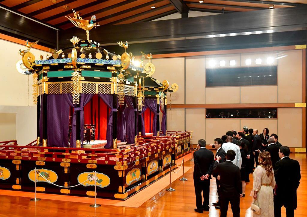 高御座(手前)や御帳台を見る参列者たち =22日午後7時48分、皇居・宮殿「松の間」(代表撮影)