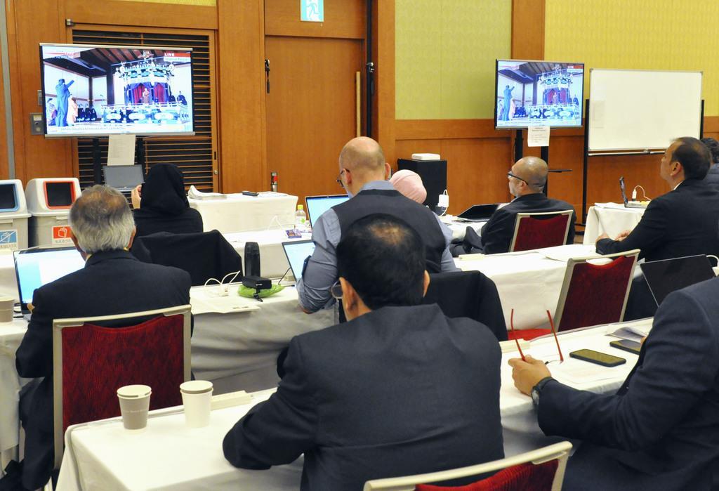 天皇陛下の「即位礼正殿の儀」で、安倍首相による万歳三唱の中継映像を見つめる海外メディアの記者=22日午後、東京都港区