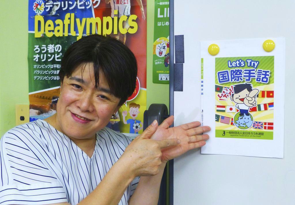 全日本ろうあ連盟が発行する国際手話の学習本を紹介する吉野幸代理事=東京都新宿区