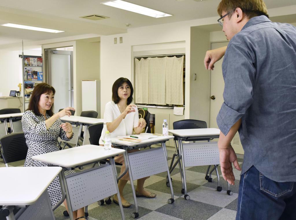 国際手話中級講座で学ぶ青塚昌子さん(左)。右は講師の砂田武志さん=東京都千代田区
