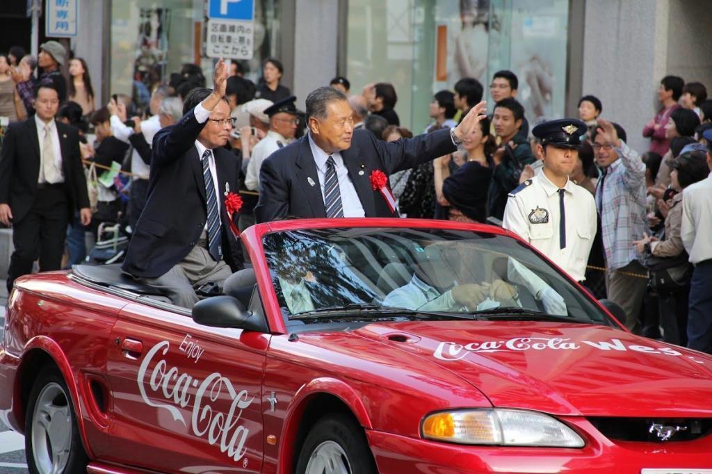 平成24年に福岡市で開かれたラグビー愛好家による国際親善大会に合わせ、市内をパレードする末吉紀雄氏(左)と森喜朗元首相(コカ・コーラボトラーズジャパン提供)