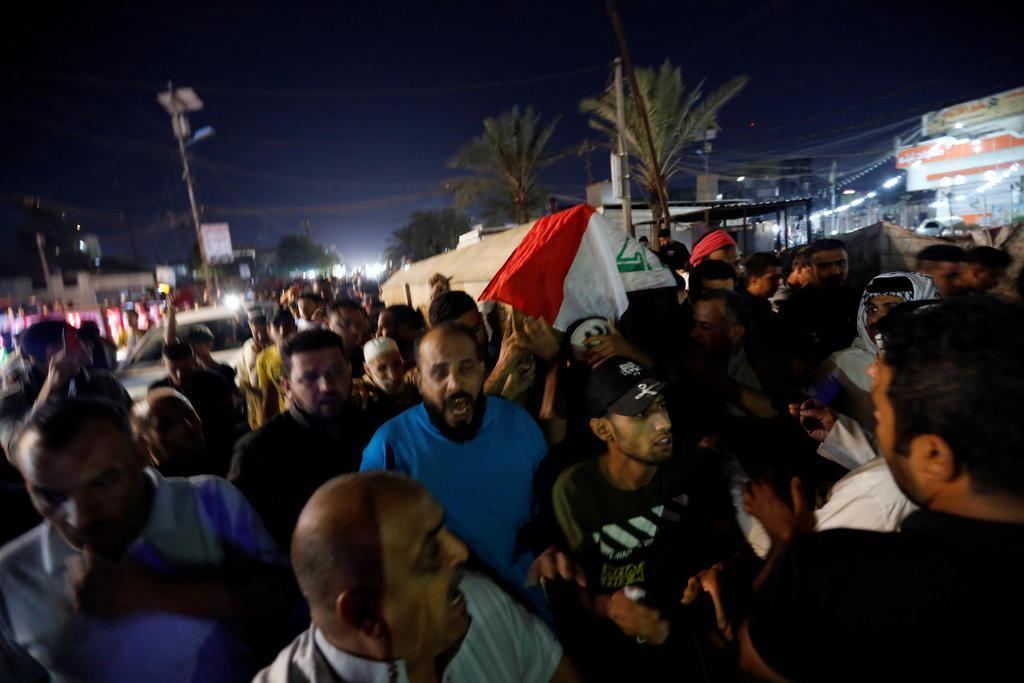 イラク・バグダッドで、死亡した反政府デモ参加者のひつぎを運ぶ人たち=10月25日(ロイター)