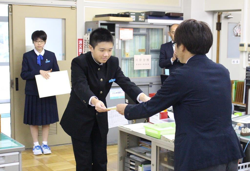 佳作に選ばれ、表彰状を受け取る杉田誠さん(中央)=29日、新潟市中央区