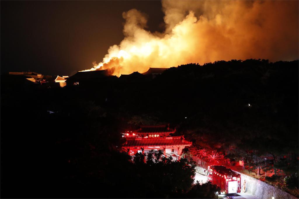 煙が上がる首里城付近。手前は守礼門=31日午前5時7分、那覇市