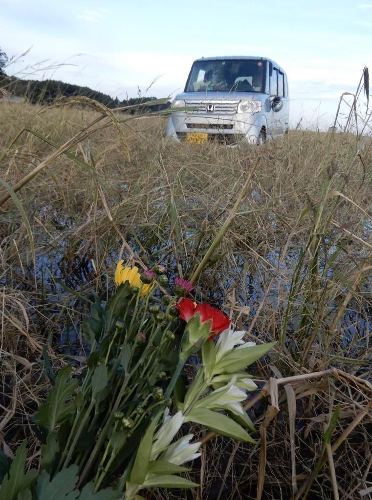 花沢美保子さんらが乗っていたとみられる軽乗用車。現場には花が手向けられていた=27日、福島県相馬市和田