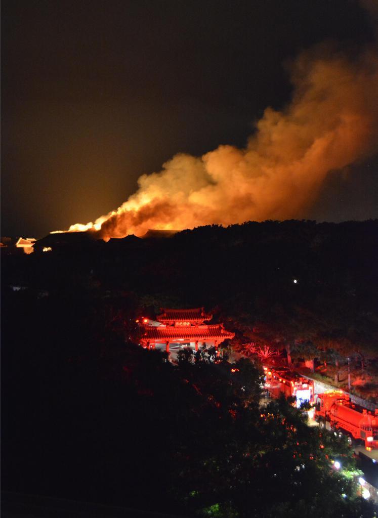 首里城から上がる煙。手前は守礼門=31日午前4時50分ごろ、那覇市