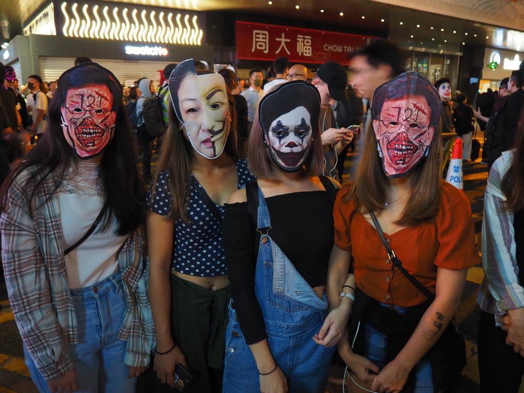 香港の繁華街で31日、政府高官らの面を付けてデモに参加する女子大生たち=(藤本欣也撮影)