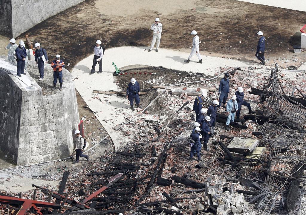 火災で焼失した首里城の正殿付近を調べる沖縄県警の捜査員ら=1日午後0時11分、那覇市(共同通信社ヘリから)