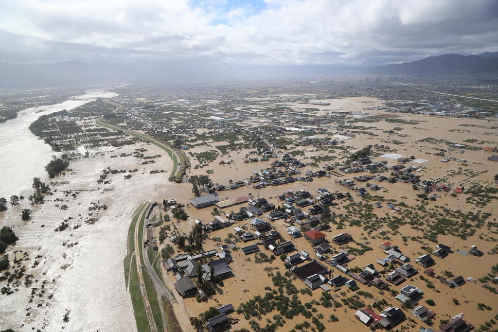台風19号による大雨で千曲川(左)が決壊した現場。濁流が住宅地に流れ込んだ=10月13日、長野市(本社ヘリから、恵守乾撮影)